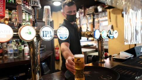 A member of staff serves a drink, as pubs, cafes and restaurants in England reopen indoors under the latest easing of the…