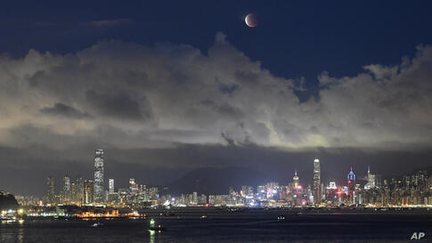 The moon rises over the Victoria Harbour in Hong Kong, Wednesday, May 26, 2021. The first total lunar eclipse in more than two…