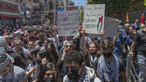 Palestinians chant slogans while taking part in an anti-Israel demonstration during a general strike in the West Bank city of…