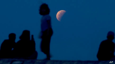 Residents watch the lunar eclipse at Sanur beach in Bali, Indonesia on Wednesday, May 26, 2021. The total lunar eclipse, also…