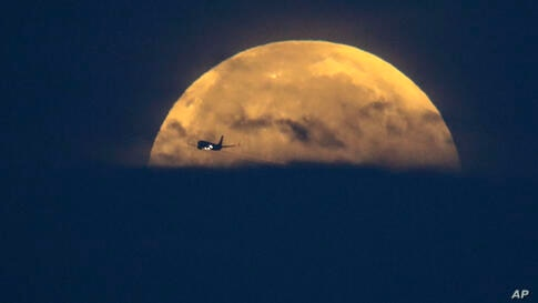 An airplane flies past as the full-moon sets over Santa Monica Beach in Santa Monica, Calif., Wednesday, May 26, 2021. The…