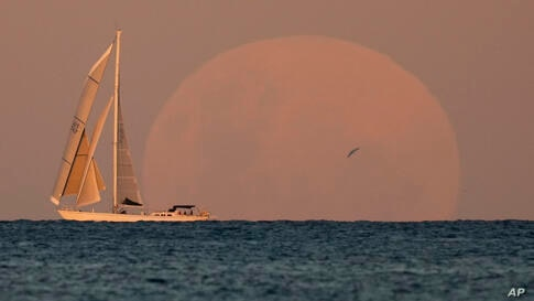 A yacht sails past as the moon rises in Sydney Wednesday, May 26, 2021. A total lunar eclipse, also known as a Super Blood Moon…