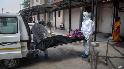 Health workers in protective suits shift the body of a COVID-19 victim at a government hospital in Gauhati, India, Monday, May…