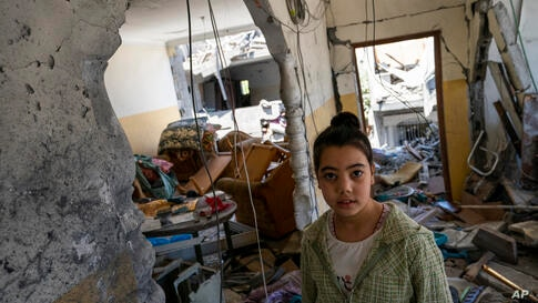 Saja Qatamesh, 9, stands in her home, that was severely damaged after an air-strike destroyed a neighboring building prior to a…