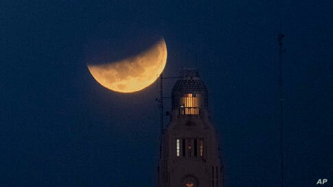 The moon sets behind the Montevideo port, in Uruguay, Wednesday, May 26, 2021, during a lunar eclipse, also known as a super…