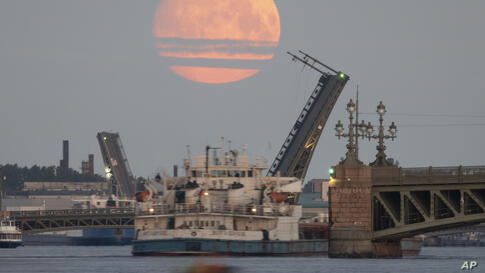 A cargo ship travels past as drawbridges rise above the Neva River, with the moon in the sky, in St. Petersburg, Russia, early…