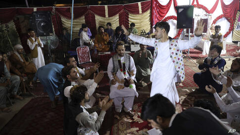 Zameer Ahmad, an Afghan groom, center, with his friends who were doing traditional dancing during his wedding ceremony at his…
