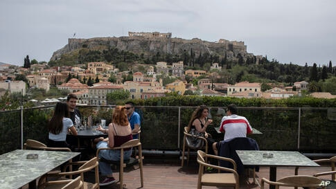 People sit in on a cafe terrace, in the Monastiraki district of Athens, with the ancient Acropolis hill in the background,…