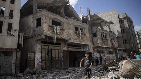 Palestinians inspect damaged houses that were hit in early morning Israeli airstrikes, in Gaza City, Monday, May 17, 2021. (AP…