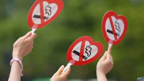 Activists hold no-smoking signs during a campaign on a street to mark World No Tobacco Day in Seoul, South Korea, Monday, May…