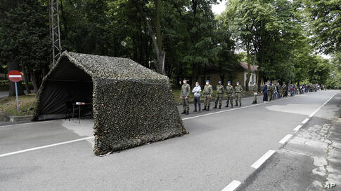 Serbian army soldiers wait in line to receive the Sinopharm COVID-19 vaccine at the army barracks in Belgrade, Serbia, Thursday…