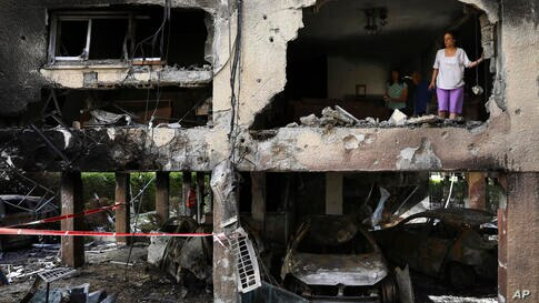 Members of Sror family inspect the damage of their apartment after it was hit by a rocket fired from the Gaza Strip over night…