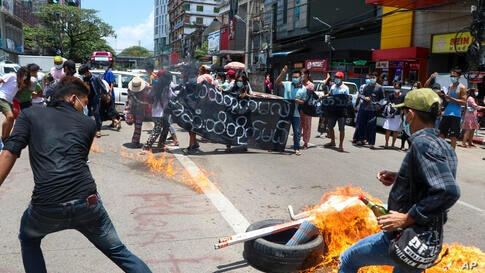 Anti-coup protesters burn tires and chant slogans with banner read ''The Kamayut strike will be fight for to the end when we…
