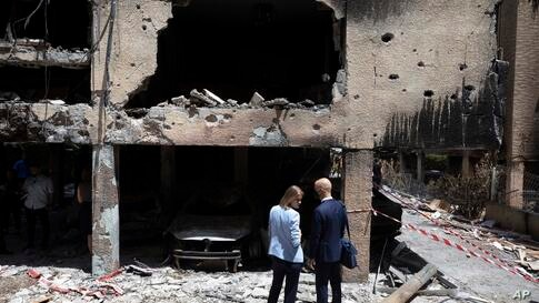 People look at the damage to a house at the site of a rocket attack prior to a visit by foreign ministers in central Israeli…