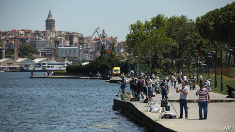 Backdropped by the iconic Galata Tower, people walk and fish on the Golden Horn leading to the Bosphorus Strait separating…