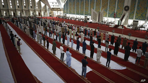 People perform afternoon prayers at the Grand Faisal Mosque, in Islamabad, Pakistan, Monday, May 3, 2021. (AP Photo/Anjum…