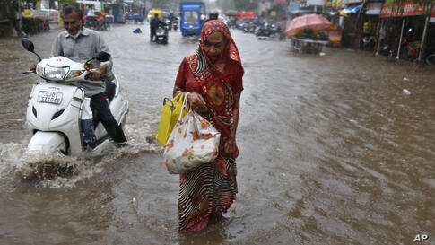 A motorist and a woman wade through a waterlogged street after heavy rains in Ahmedabad, India, Tuesday, May 18, 2021. Cyclone…