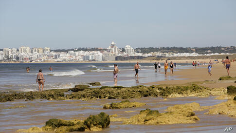 People walk on the beach in Albufeira, in Portugal's southern Algarve region, Tuesday, May 18, 2021. British vacationers began…