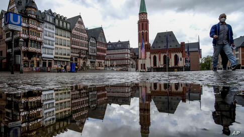 Buildings at the Roemerberg square are reflected in a puddle as a man wearing a face mask walks by in Frankfurt, Germany,…