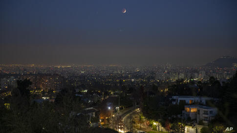 A lunar eclipse occurs over Santiago, Chile, early Wednesday, May 26, 2021. Wednesday's total lunar eclipse combines with a…
