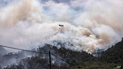 A military helicopter drops water over a forest near the village of Schinos, Corinth, Greece, on Thursday, May 20, 2021. A…