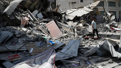A man inspects the rubble of destroyed residential building which was hit by Israeli airstrikes, in Gaza City, Thursday, May 20…
