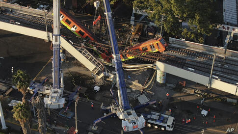 An aerial view of subway cars dangle at an angle from a collapsed elevated section of the metro, in Mexico City, Tuesday, May 4…