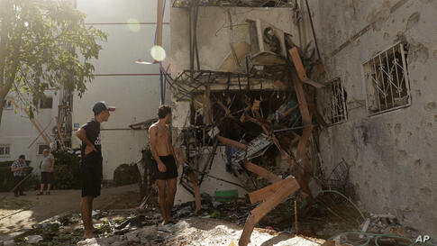 People look at a residential building after it was hit by a rocket fired from the Gaza Strip, in Ashdod, southern Israel,…