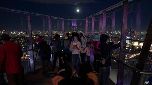Visitors to the Olympics Tower try to catch a view of the lunar eclipse in Beijing on Wednesday, May 26, 2021. The first total…