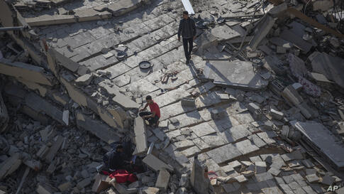 Palestinians inspect the rubble of their destroyed home after being hit by Israeli airstrikes in town of Beit Lahiya, northern…