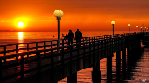 People walk on the pier at the Baltic Sea in Scharbeutz, Germany, as the sun rises Monday, June 7, 2021. (AP Photo/Michael…