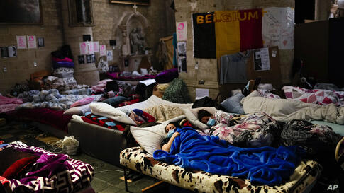 Women on hunger strike rest as they occupy with others the Saint-Jean-Baptiste-au-Beguinage church in Brussels, Monday, June 7,…