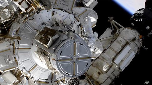 This photo provided by NASA shows astronauts NASA's Shane Kimbrough and France's Thomas Pesquet during a space walk outside the…