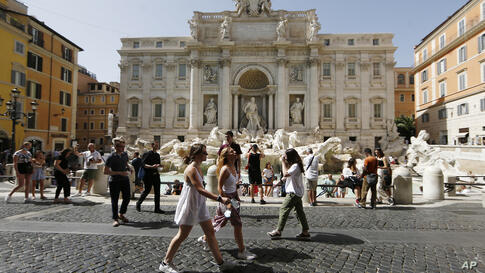 People gather and walk in front of the Trevi fountain in Rome, Monday, June 28, 2021. Italians took off their face masks and…