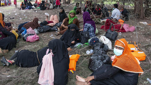 Ethnic Rohingya people rest on a beach after their boat was stranded on Idaman Island in East Aceh, Indonesia, Friday, June 4,…