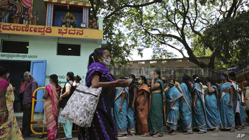 Women wearing face masks as a precaution against the coronavirus line up for free food provided by a Hindu temple in Bengaluru,…