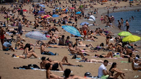 People sunbathe on the beach in Barcelona, Spain, Tuesday, June 8, 2021. Spain is jumpstarting its summer tourism season by…