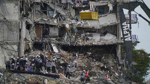 Search and rescue personnel work atop the rubble at the Champlain Towers South condo building, where scores of people remain…