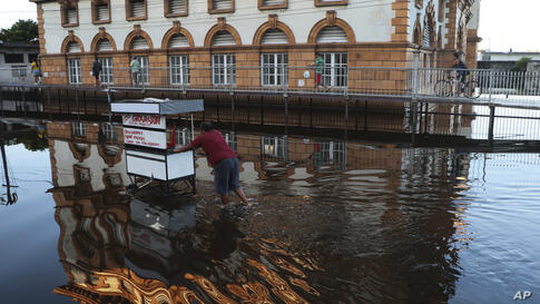 A street vendor pushes his mobile stall through a street flooded by the Negro River, in downtown Manaus, Amazonas state, Brazil…