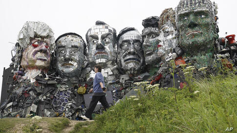 A visitor walks past a sculpture created out of e-waste in the likeness of Mount Rushmore and the G7 leaders on a hill in Hayle…