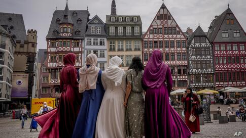 A bride, center, and her friend pose for pictures after a wedding in the town hall on the Roemerberg square in Frankfurt,…