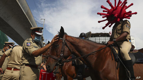 A policeman rides a horse wearing a virus-themed helmet during a COVID-19 awareness drive in Hyderabad, India, Tuesday, June 1,…