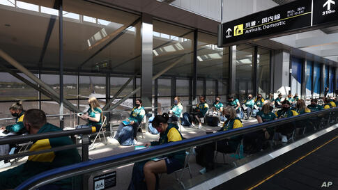 Australian softball national team players wait for the antigen test after arriving at the Narita International Airport in…