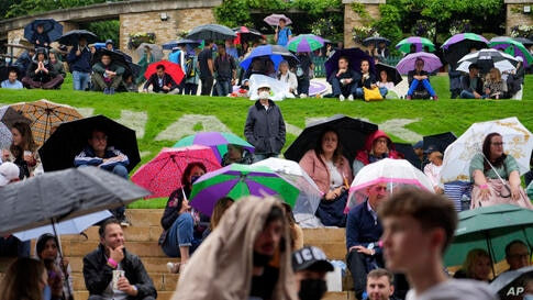 Spectators shelter under umbrellas during a rain delay on day one of the Wimbledon Tennis Championships in London, Monday June…