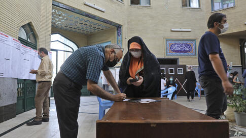 A couple fill out their ballot papers at a polling station during the presidential elections in Tehran, Iran, Friday, June 18,…