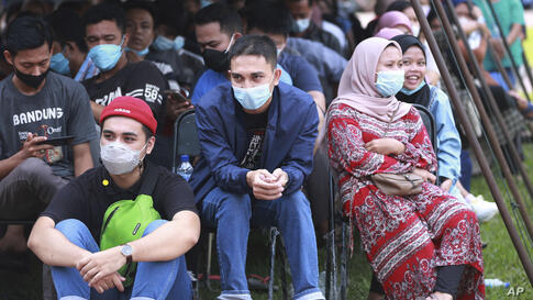 People sit under a tent as they wait for theirCOVID-19  Sinovac vaccine during a mass vaccination held by the Indonesia…