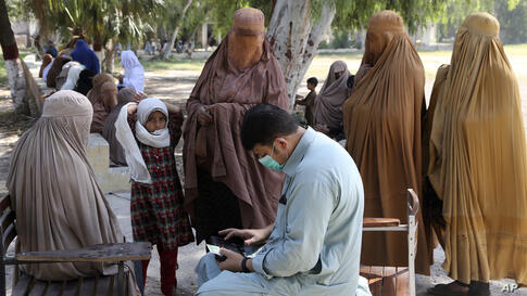Women wait to receive cash vouchers from an officer under the government's Ehsaas Emergency Cash program for families in need,…