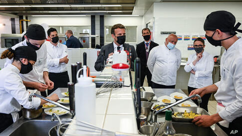 French President Emmanuel Macron looks at students cooking next to Chefs Anne-Sophie Pic, second right, and Chef Thierry Marx,…