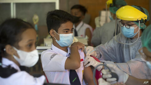 Teenagers receive a shot of the Sinovac vaccine for COVID-19 during a vaccination campaign at a school in Denpasar, Bali,…