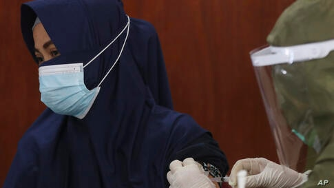 A woman receives a shot of the Sinovac vaccine for COVID-19 during a vaccination campaign in Jakarta, Indonesia, Monday, July…